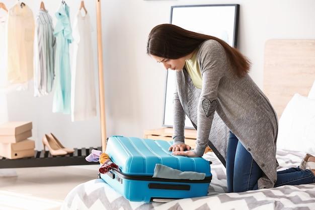 Donna che cerca di chiudere la valigia con un sacco di cose. concetto di viaggio