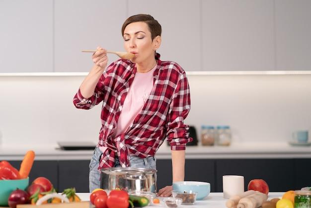 Donna che prova un piatto cucinato usando un cucchiaio di legno lungo.