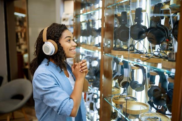 Donna che prova sulle cuffie nell'archivio del sistema di altoparlanti. persona di sesso femminile nel negozio di audio, vetrina con auricolari, acquirente nel negozio multimediale