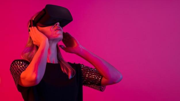 Donna che prova un nuovo dispositivo con luce rosa