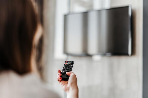 Donna che accende la tv con un telecomando a casa nell'appartamento