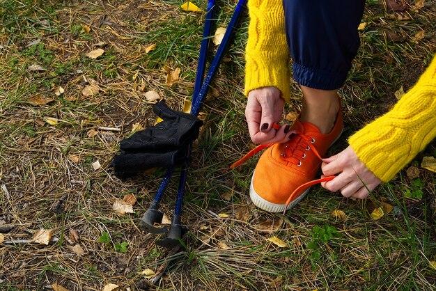 Donna che allaccia le scarpe nella foresta Foto Premium