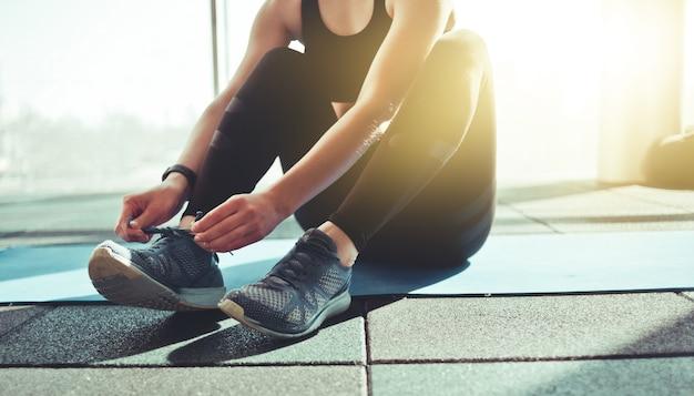 Donna che lega i lacci delle scarpe da ginnastica sportive seduto su una stuoia in palestra