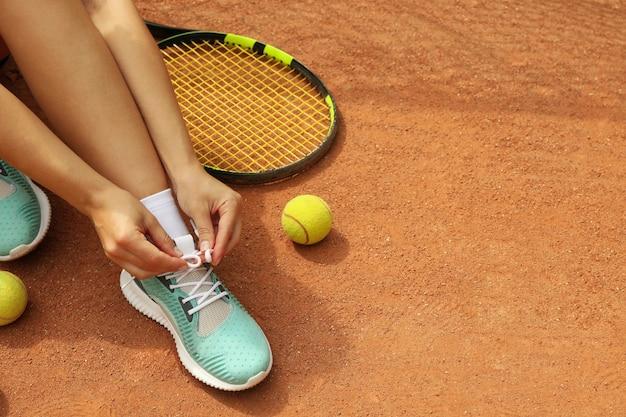Donna che lega i lacci delle scarpe sul campo in terra battuta con racchetta e palline da tennis