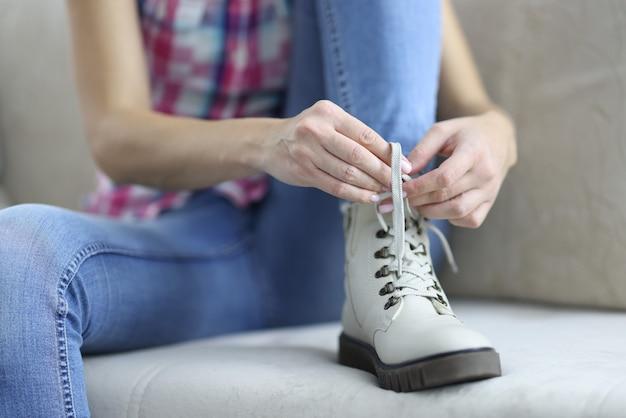 Donna che lega i lacci delle scarpe sui nuovi stivali in pelle demi.