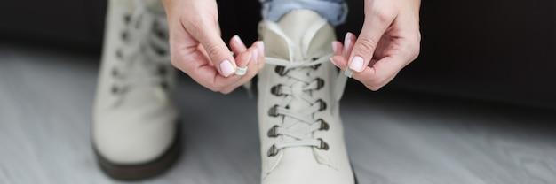 Donna che lega i lacci delle scarpe sul primo piano bianco delle scarpe calde