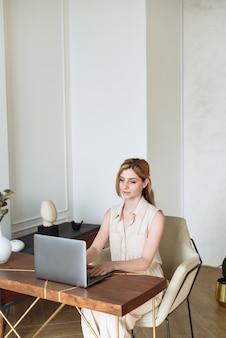 Una donna digita su un laptop e si arrampica e comunica sui social network. una ragazza sta studiando