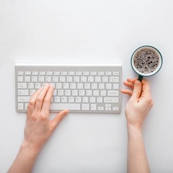 Donna che digita sulla tastiera del computer bevendo caffè sul posto di lavoro. spazio di lavoro desktop dell'ufficio con le mani