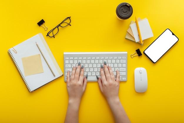 Donna che digita sulla tastiera del computer sul posto di lavoro su sfondo giallo a colori. area di lavoro desktop dell'ufficio con mani femminili, fornitori di ufficio mockup smartphone tazza di caffè, occhiali. vista dall'alto piatta.