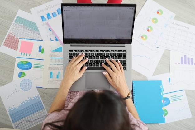Donna che digita sulla tastiera del laptop tra la serie di documenti vista dall'alto