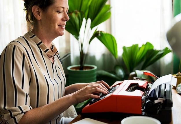 Donna che scrive su una retro macchina da scrivere