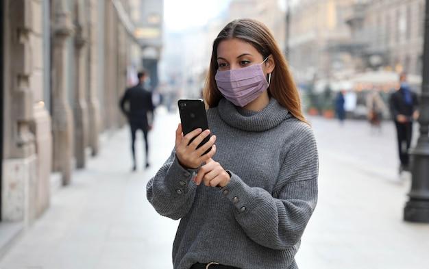 Donna che digita su smart phone in strada di città che indossa la protezione della maschera per il viso