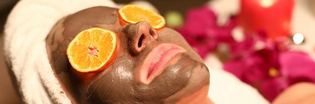 La donna si sottopone a corso di benessere e pulizia del viso. liscivia del cliente sul lettino da massaggio con i capelli avvolti in un asciugamano, maschera al carbone sul viso e cerchi arancioni davanti ai suoi occhi.