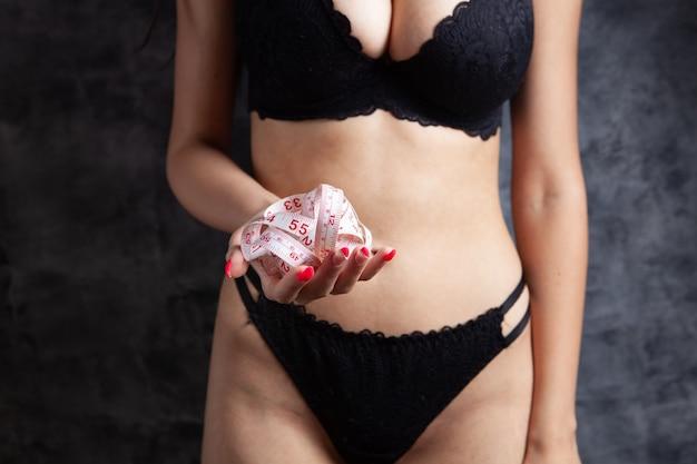 La donna in biancheria intima tiene in mano un metro a nastro