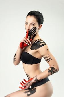 La donna in mutande imbrattata di vernice nera su sfondo bianco