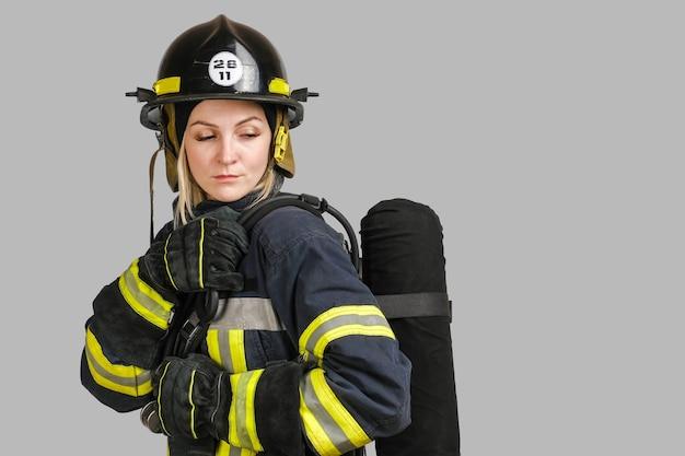 Donna in uniforme di pompiere in posa di profilo con serbatoio d'aria