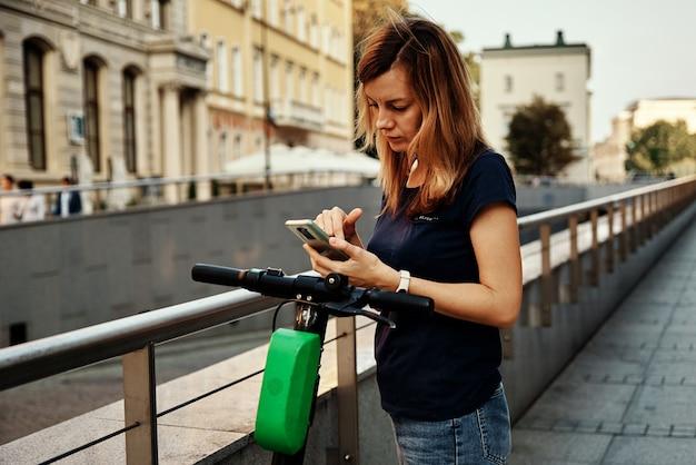 La donna sblocca lo scooter elettrico a noleggio con un'applicazione per smartphone