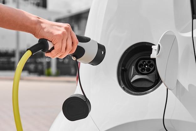 Donna che scollega un caricabatterie da una presa per auto elettrica. veicolo ecologico a zero emissioni