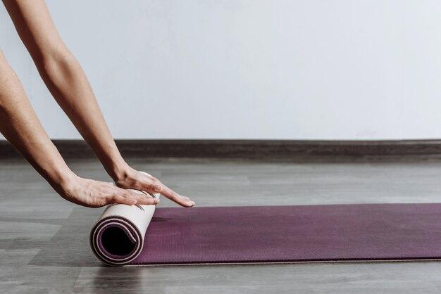 Materassino yoga di srotolamento della donna su priorità bassa bianca