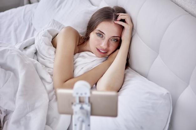 La donna usa il supporto per smartphone a mani libere quando è sdraiata a letto in camera da letto e guarda video o film
