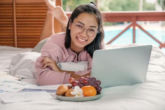 La donna usava videoconferenze con laptop e mangiava frutta a letto cibo sano e lavorava da casa concept