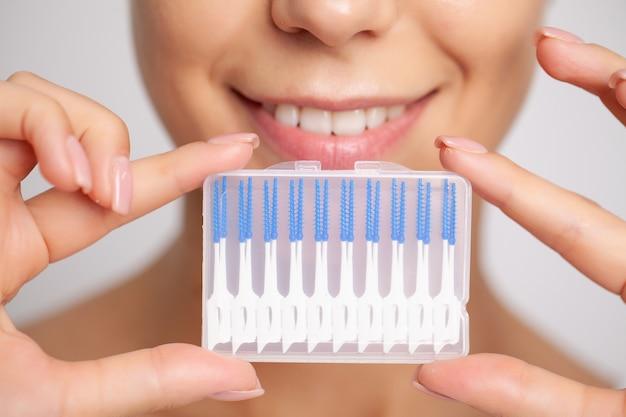 La donna usa gli spazzolini per pulire gli spazi interdentali.