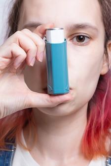 La donna usa l'inalatore per curare l'asma. giornata mondiale dell'asma. concetto di cura delle allergie