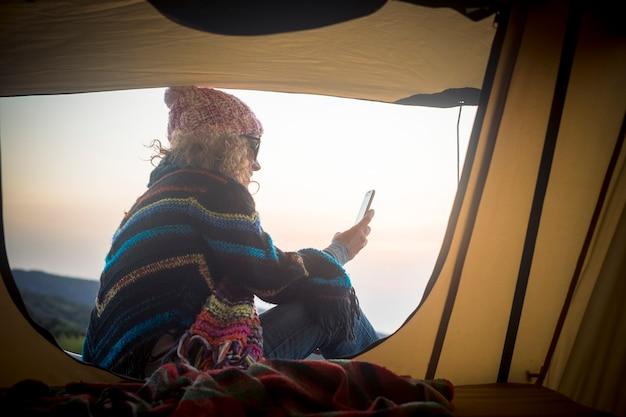 La donna usa la connessione internet e il telefono cellulare fuori dalla tenda in natura