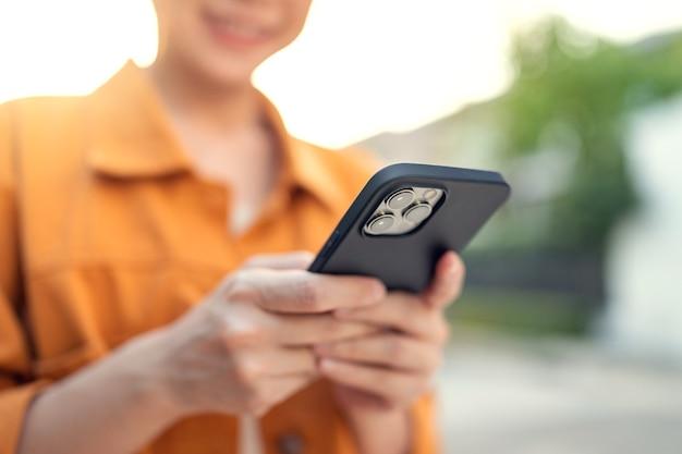 La donna utilizza il telefono cellulare e la tecnologia internet nel parco all'aperto Foto Premium