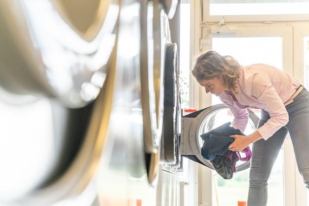 La donna usa una lavanderia pubblica. copia spazio