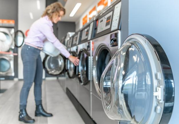 La donna usa una lavanderia pubblica