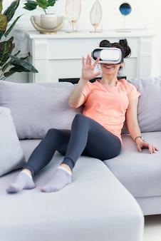 La donna utilizza occhiali vr a casa sul divano. tecnologie del futuro.