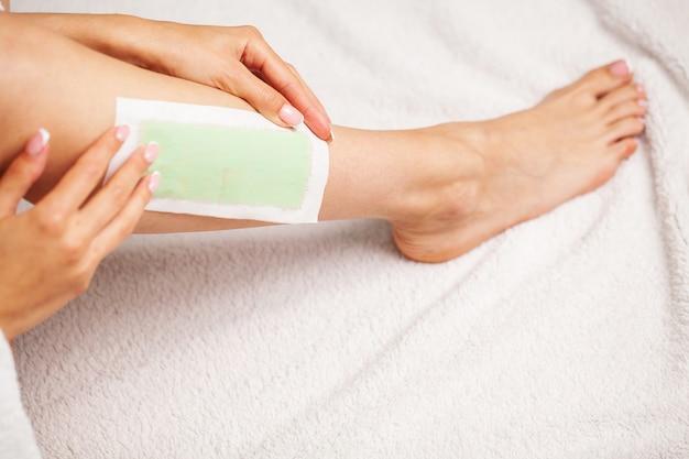 La donna usa del nastro cerato per rimuovere i peli sulle gambe