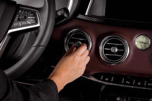 Donna che per mezzo del condizionatore d'aria dentro un'automobile