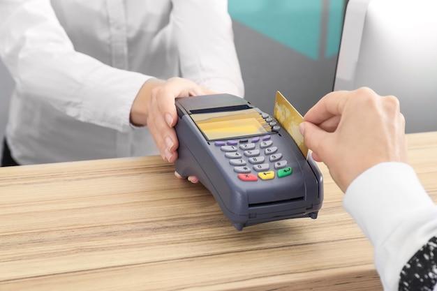 Donna che utilizza il terminale della banca per il pagamento con carta di credito al chiuso