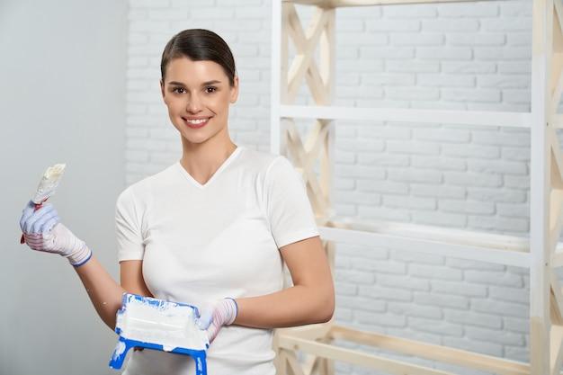 Donna che usa pennello e vassoio di vernice per rinfrescare il rack