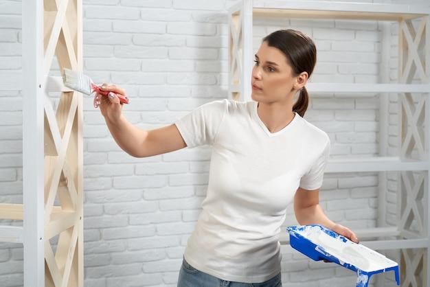 Donna che usa il pennello e il colore bianco mentre dipinge lo scaffale
