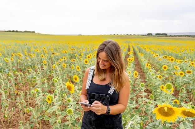 Una donna che utilizza un telefono cellulare tra i girasoli.