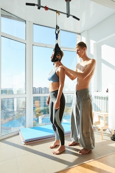 Donna che utilizza il dispositivo di trazione cervicale nello studio di yoga