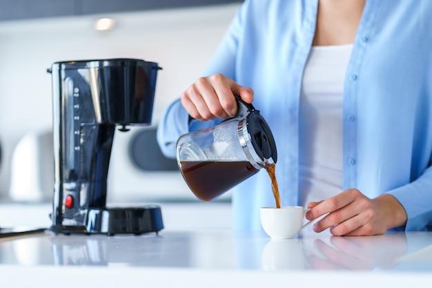 Donna che per mezzo della macchinetta del caffè per produrre e fare il caffè a casa. frullatore per caffè ed elettrodomestici da cucina per bevande calde