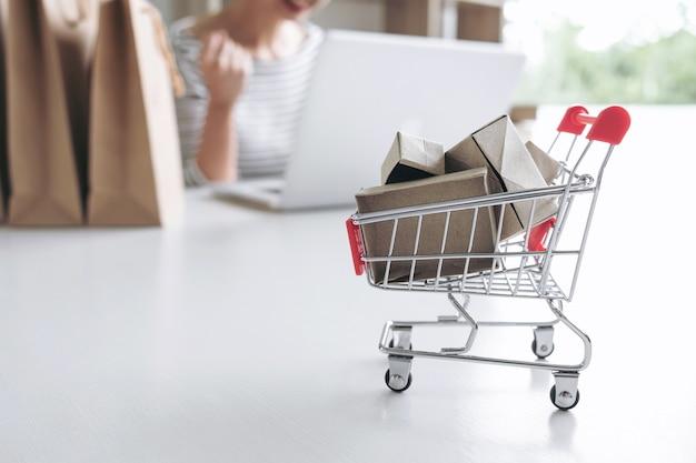 Donna che usando i pagamenti del registro della carta di credito acquisto online