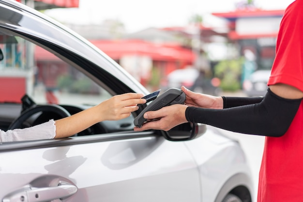 Donna che utilizza la carta di credito con il terminale di pagamento con carta per pagare il rifornimento di benzina alla stazione di servizio