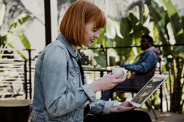 Donna che utilizza una tavoletta digitale in un bar