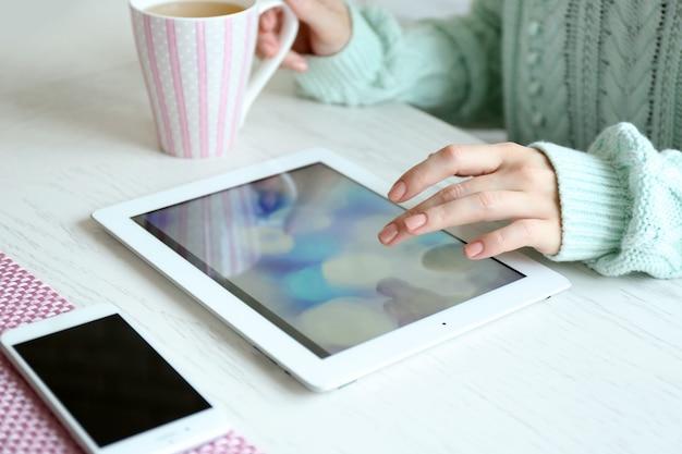 Donna che utilizza tavoletta digitale sul primo piano del tavolo