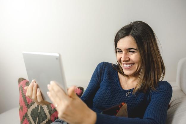 Donna che utilizza la tavoletta digitale per una videochiamata, felice e sorridente durante la chiamata nel suo tempo libero