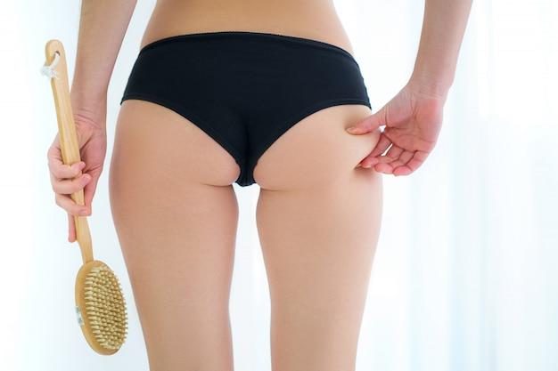 Donna che utilizza una spazzola di legno asciutta per massaggiare e spazzolare il culo, i glutei e il sedere della pelle per prevenire e curare la cellulite e i problemi del corpo a casa. salute della pelle
