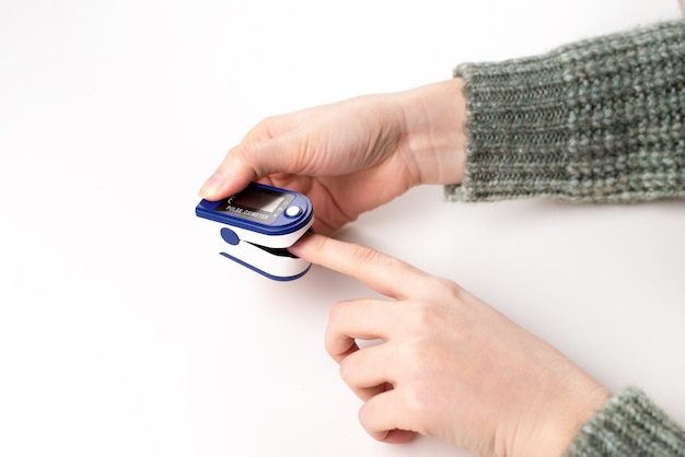 Donna che utilizza pulsossimetro a punta di dito su sfondo bianco, primi piani.