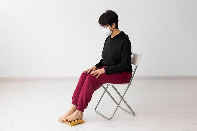 Donna che utilizza un dispositivo di massaggio ai piedi
