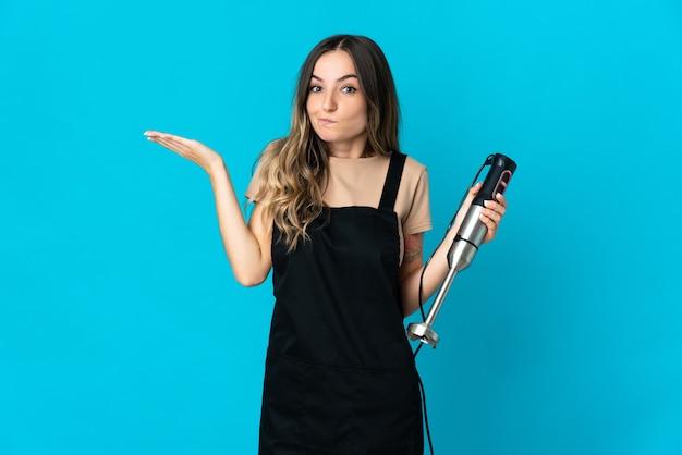 Donna che utilizza il frullatore a immersione isolato avendo dubbi mentre si alzano le mani