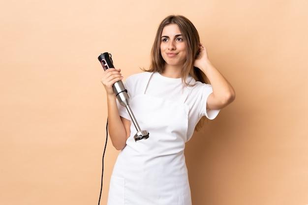 Donna che utilizza il frullatore a immersione sulla parete isolata avendo dubbi